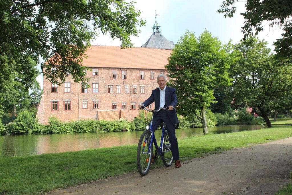 Rainer Rempe (Landrat Kreis Harburg) auf einem Fahrrad vor einem Schloss.
